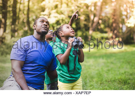Young father with son and daughter bird watching in eco forest camp - Stock Photo