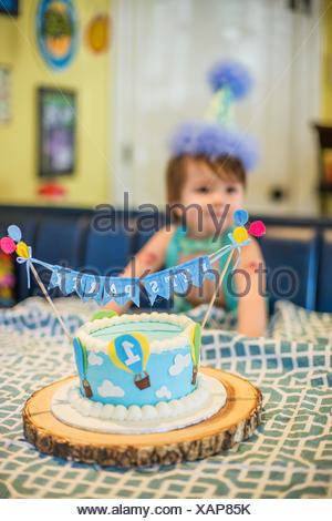 Baby Boy Wearing Party Hat Smashing First Birthday Cake At Table