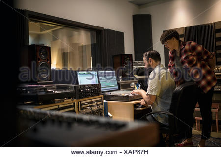 Music producers working at sound mixer in recording studio - Stock Photo