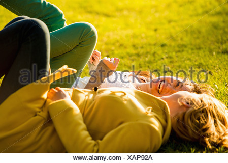 Two young women lying back in park - Stock Photo