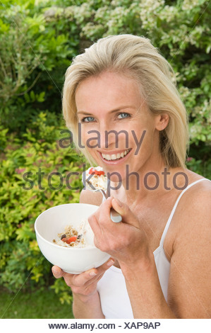 Woman eating fruit and muesli - Stock Photo