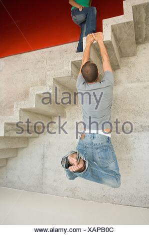 Man hanging onto concrete staircase - Stock Photo