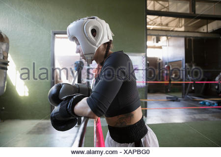 Strong, tough female boxer in protective headwear and boxing gloves, resting at rope in boxing ring - Stock Photo