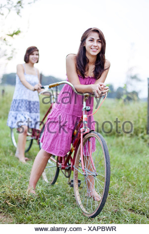 Two sisters stand with their bikes in a field. - Stock Photo
