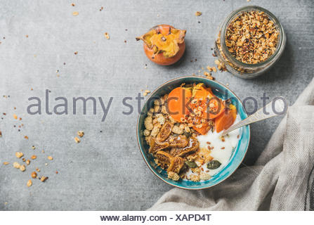 Healthy breakfast concept. Oatmeal, quinoa granola with yogurt, dried fruit, seeds, honey, persimmon in bowl over grey concrete background, top view, - Stock Photo