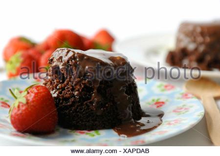 Chocolate sponge pudding with fresh strawberries - Stock Photo