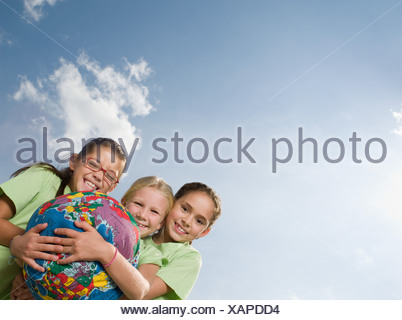 Girls holding an inflatable planet earth - Stock Photo