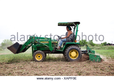 A woman drives a tractor in a field on her urban farm in Denver, CO. - Stock Photo