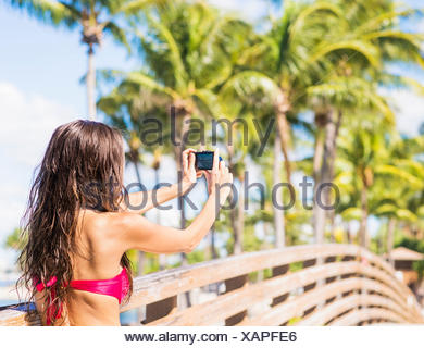 USA, Florida, Jupiter, Young woman photographing wooden bridge - Stock Photo