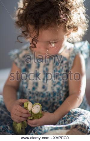 Young girl, sitting on floor, playing with toy - Stock Photo