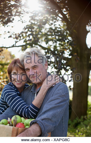 Portrait of smiling couple with bushel of apples hugging in orchard - Stock Photo