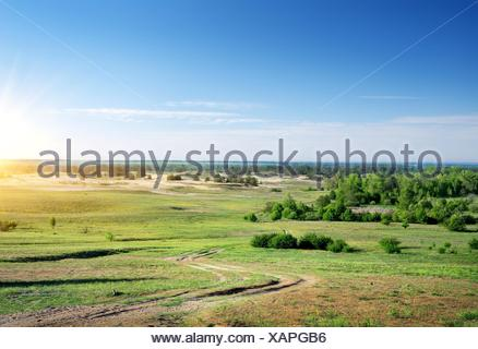 Country road through the plain at sunrise. - Stock Photo