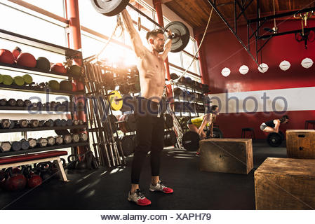 Bodybuilder lifting barbell in gym - Stock Photo