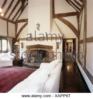 White sofa and armchair in large barn conversion living room with high beamed apex ceiling  and red patterned oriental rug - Stock Photo