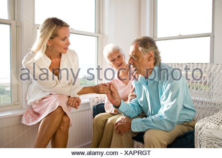 Adult daughter having serious discussion with senior parents - Stock Photo