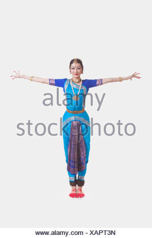 Portrait of young woman with arms outstretched performing Bharatanatyam against white background - Stock Photo