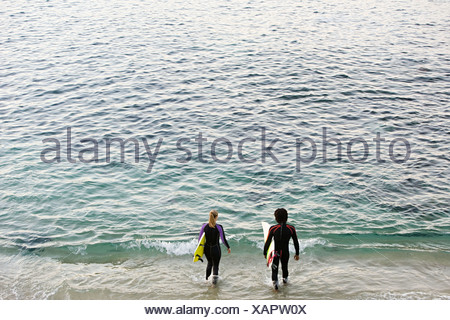 Surfer couple going into the sea - Stock Photo