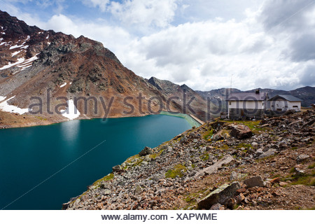 View over Green Lake with Hoechster Huette alpine hut while descending from Zufrittspitz Mountain towards the Ulten Valley - Stock Photo