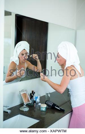 woman applying face powder in the bathroom mirror - Stock Photo
