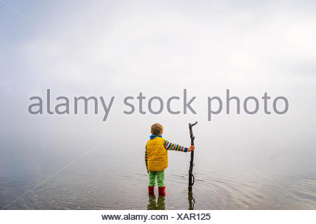 Boy holding stick, standing in ocean - Stock Photo