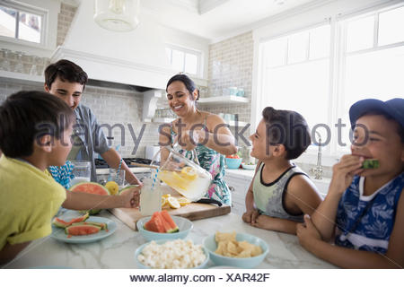 Mother pouring lemonade for sons in kitchen - Stock Photo