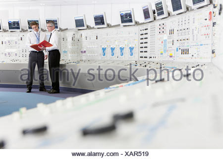Engineers discussing paperwork in control room of nuclear power station - Stock Photo