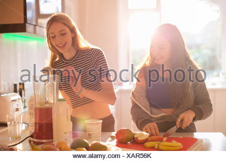 Teenage girls making smoothie in sunny kitchen - Stock Photo