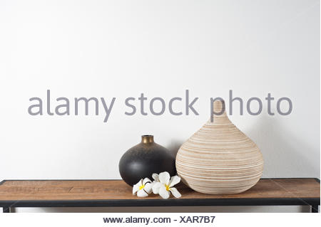 Empty Vases Decorated With Frangipani Flower Over Side Board Stock