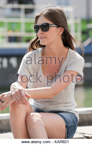Woman sitting on the ledge of a canal, Canal St Martin, Paris, Ile-de-France, France - Stock Photo