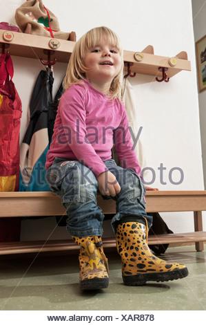 Little Girl Sitting On Bench In Nursery School, Kottgeisering, Bavaria, Germany, Europe - Stock Photo