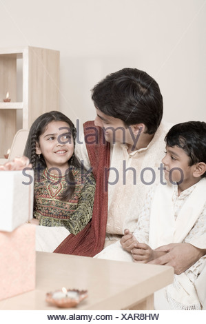 Young man sitting with his son and daughter behind lamps lit on a wooden table - Stock Photo