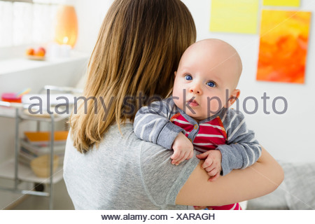 Mother holding baby son over shoulder - Stock Photo