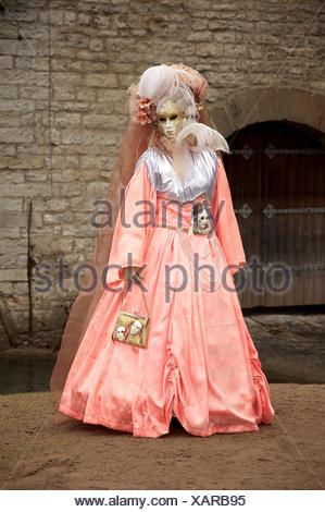 Eine Junge Frau in einem Kostüm steht vor einer Mauer - Stock Photo