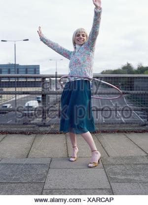 Woman playing with hula hoop on motorway bridge - Stock Photo