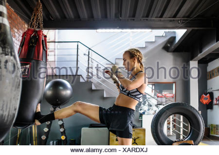 Side view photograph of female kickboxer kicking punching bag, Seminyak, Bali, Indonesia - Stock Photo