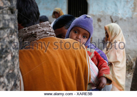 Young child on the arm of his father, villagers near Rajbiraj, Terai region, Nepal, Asia - Stock Photo