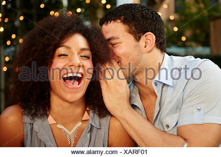 Young man whispering to laughing woman at garden party - Stock Photo