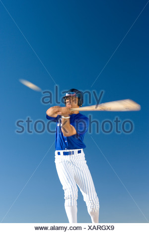 Baseball batter standing against clear blue sky, hitting ball, front view, low angle view blurred motion - Stock Photo
