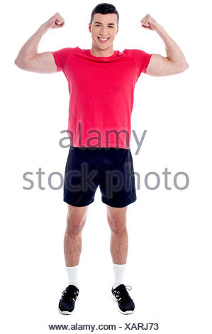Happy young athlete raising his fists in excitement - Stock Photo