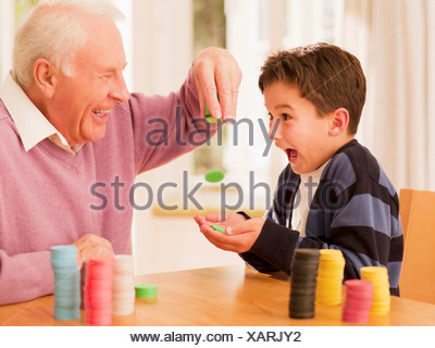 Grandfather dropping poker chips into grandson's hands - Stock Photo