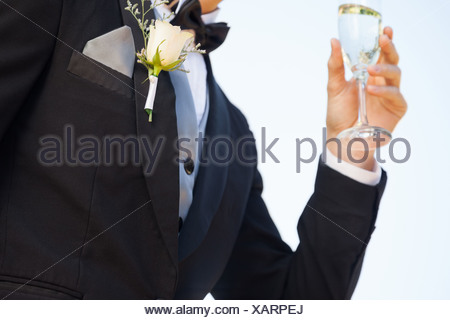 Mid section of flowers on lapel of male as he holds champagne glass - Stock Photo