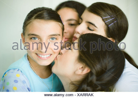 Four young female friends, three kissing one girl's cheek - Stock Photo