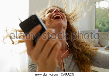 Woman dancing to music on smartphone - Stock Photo