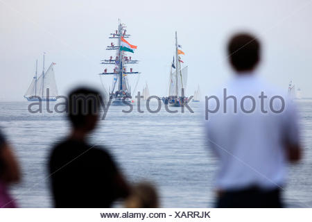 Sailing ships head to sea as people watch the Parade of Sail conclusion of the 2007 Tall Ships festival in Halifax, Nova Scotia. - Stock Photo