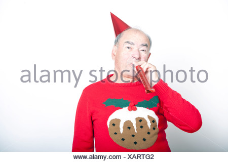 e813a9595fbf85 ... Senior adult man wearing Christmas jumper blowing party blower - Stock  Photo