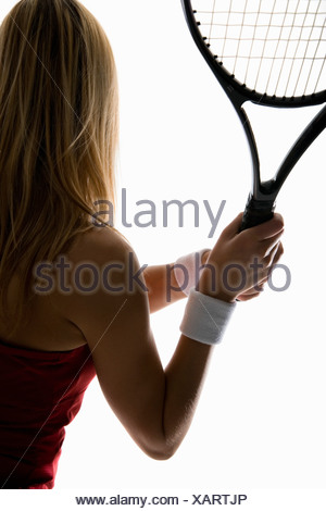 A close-up studio shot of a female tennis player holding a tennis racket - Stock Photo