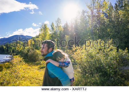 Father giving daughter a piggyback ride - Stock Photo