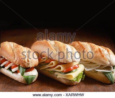 Trio of freshly baked golden vegetarian baguettes with a variety of cheese fillings with herbs and salad ingredients in a row on a wooden counter with dark copyspace behind - Stock Photo