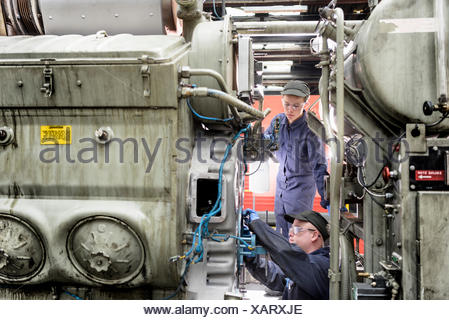 Apprentice watching engineer working on locomotive engine in train works - Stock Photo
