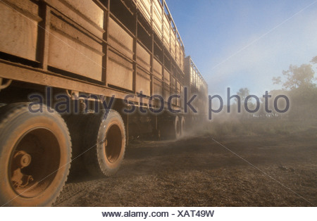 The wheels of a longhall road train churn up the dust in the outback. - Stock Photo